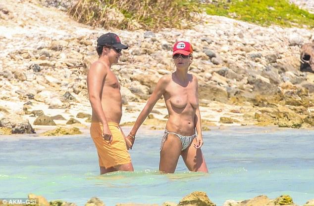 Bronzed: The supermodel wore a red baseball cap, sunglasses and a silver bikini bottom