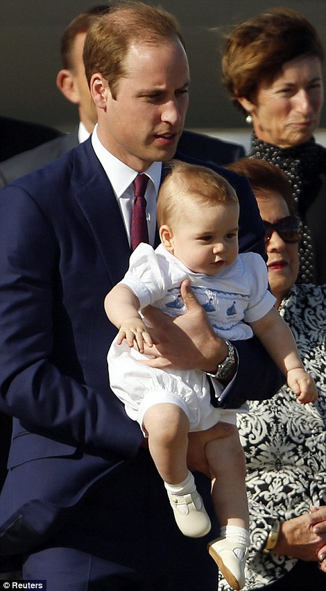 Daddy's boy: Held in his father's arms, a friendly George raised his arms in excitement as he dignitaries