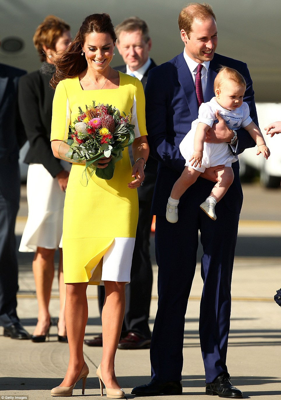 Warm welcome: Kate clutched a bunch of native Australian flowers, meanwhile William held baby George in his arms as they made their way across the tarmac