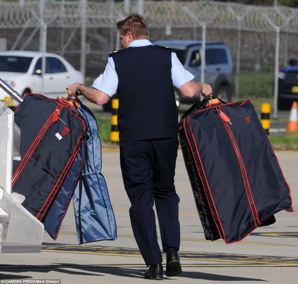 Peronsalised treament: The Duke's suits, complete with monogrammed sign, being carried off the plane in Sydney