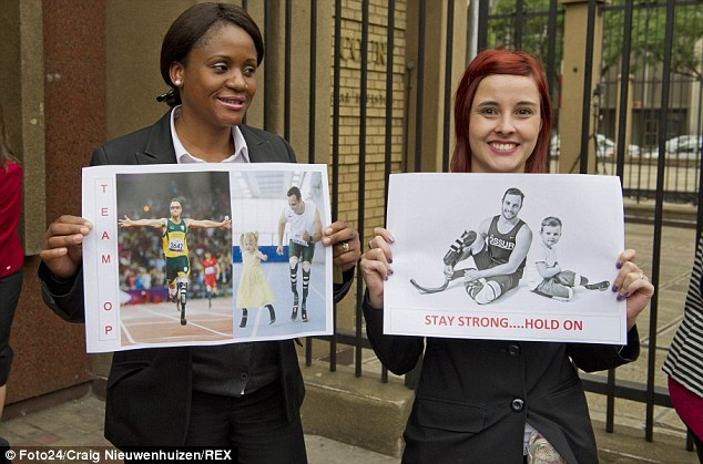 Right behind him: Supporters hold banners saying 'Team OP' and 'stay strong... hold on' as they wait for Pistorius to arrive at court