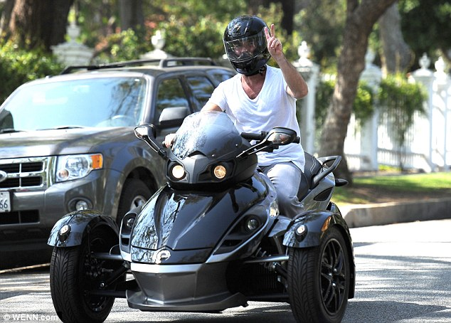 Peace out: Simon Cowell goes for a ride through Los Angeles on a three-wheeled 'Spyder' vehicle