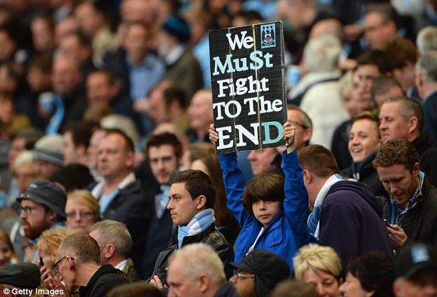 Keep on: A Manchester City fan holds up a placard