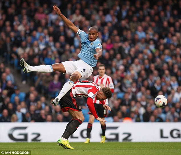 Tumble: Vincent Kompany flies over the top of Connor Wickham