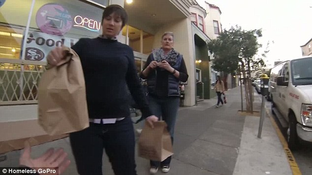 Good Samaritans: Two women bring a hot meal to the man after he has been begging outside the store