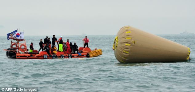 Search: Rescuers, pictured today, were still searching for victims in the sea, where an inflatable buoy marks the position of the wreckage