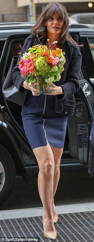 Spring in the air: Katie carried the bright bouquet as a breeze whipped her hair around