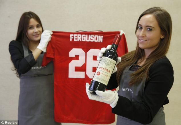 Staff at Christies auction house show off a bottle of Petrus 1988, one of 12 to go under the hammer. A retro Manchester United Champions League shirt will also be up for grabs when the three separate sales take place, one in London, another in Hong Kong and the last online