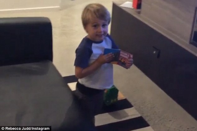 Go dad! Chris and Rebecca Judd's 2-year-old son Oscar cheered on his AFL star dad on Thursday as he was named to play his first game for the new season