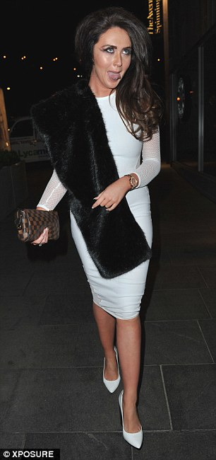 Happy-go-lucky: She carried a designer bag and wore a fur stole over her shoulder as she walked through Manchester