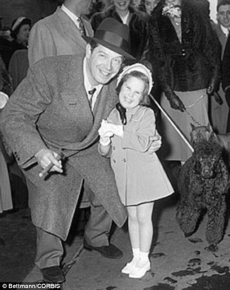 09 Apr 1950 --Little Vickie Berle, 4 1/2, reflects her daddy's famous grin a comedian, Milton Berle, stoops to hug his daughter in the midst of New York's Easter parade.