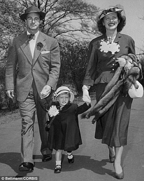 15 Apr 1949, Manhattan, New York City, New York State, USA --- Original caption: Motion picture star Bette Davis and her artist husband William Grant Sherry, spending their first Easter in New York, are shown with daughter Barbara, in her shoulder bag and Easter bonnet, taking a leisurely stroll through Central Park. They would stay over for Mr. Sherry's first New York Art Exhibit at the American British Art Center on April 22nd.