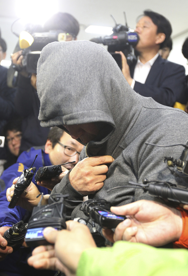 Lee Joon-seok, the captain of a sunken ferry in the water off the southern coast arrives to be investigated at Mokpo Police Station in Mokpo on Thursday