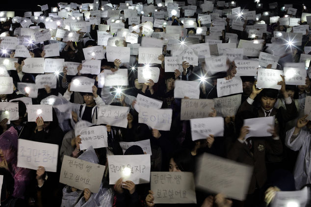"""Danwon High School students hold papers with messages such as """"come back,"""" """"miss you,"""" """"love you"""" and """"don't loose your hope"""" for their friends who are missing"""