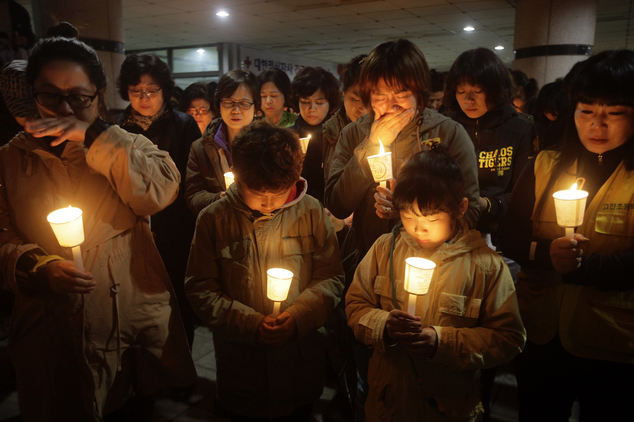 People gather to pray with candlelights for the missing passengers at Danwon High School