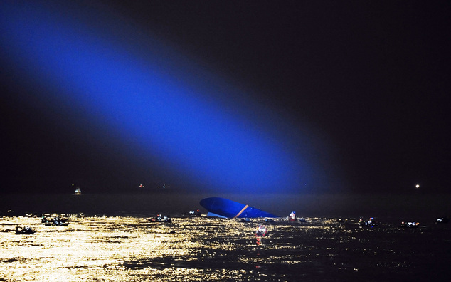 Blue search light cast by South Korean Coast Guard helicopter shows a sunken ferry in the water off coast
