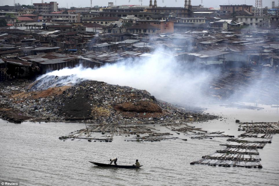 Smoke rises from the waste heap at a saw-mill at a lagoon near Makoko. The slum has sprawled out for more than 200 years since it was a small village