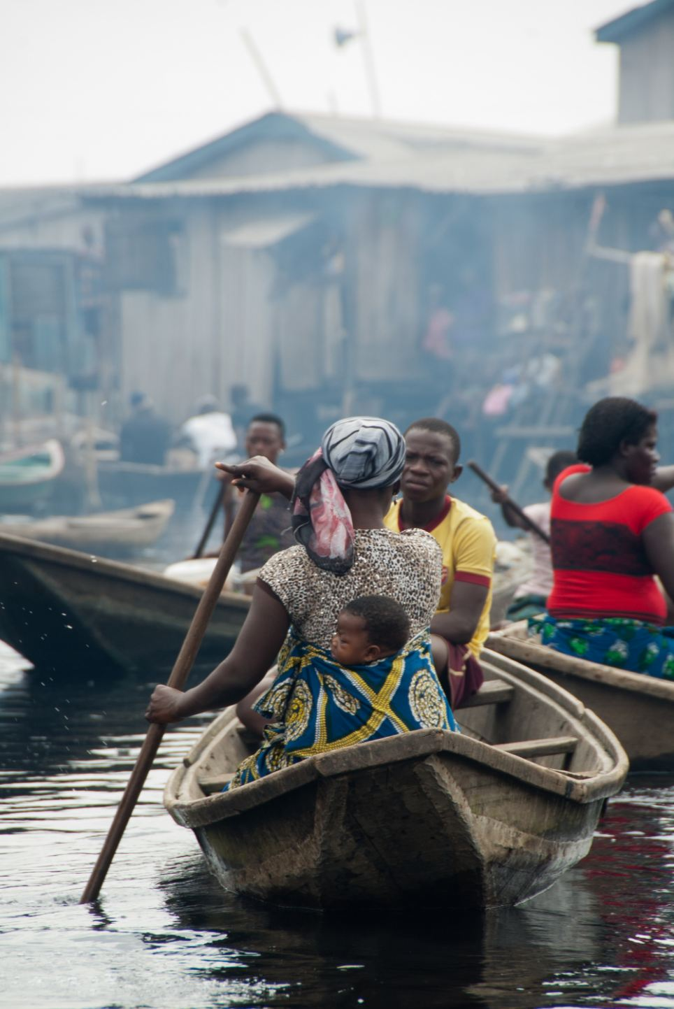 A mother backing her baby and paddling a canoe. Despite attempts by officials to demolish the slums, residents carry on with their lives