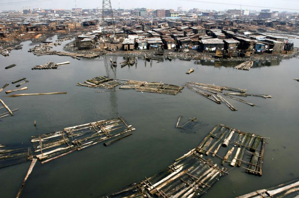 Logs of wood float in the Lagos lagoon. The lack of proper drainage systems means the water is full of rubbish