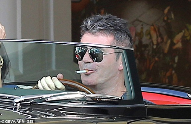 Happy: Simon's pleased look could be detected even behind the shades as he puffed happily on his cigarette