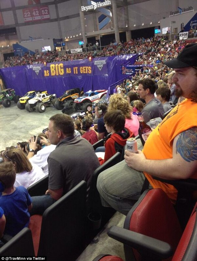 Sipping on...beer and syrup? The man pictured in an orange cutoff t-shirt above was drinking a Miller Lite and syrup out of the bottle at a monster truck rally in Lincoln, Nebraska last week