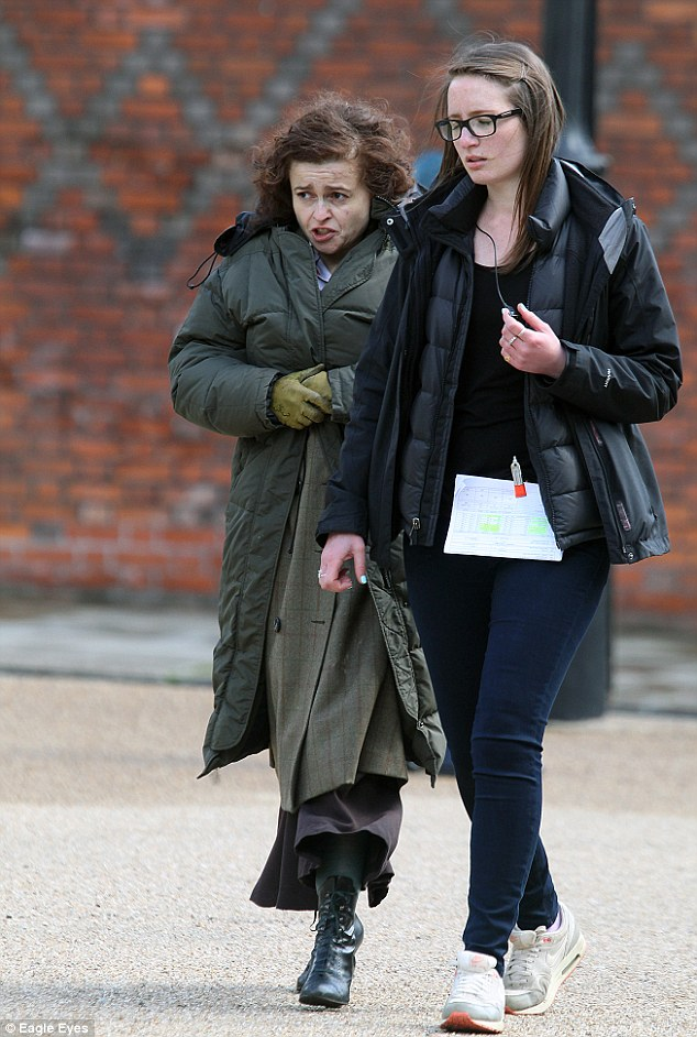 Wrapped up: Helena keeps warm in a padded coat during breaks in filming