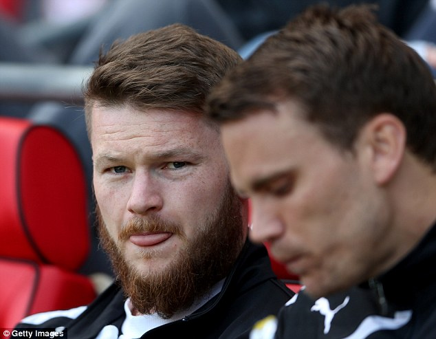 In the picture: Aron Gunnarsson (left) of Cardiff City looks on from the bench against Stoke