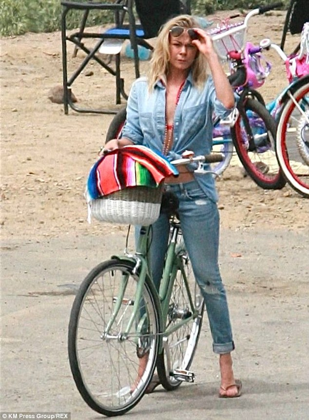 California cool: The 31-year-old musician was an eye-catching sight as she rode her bike around the RV campground at Carpinteria State Beach, leaving the buttons of her denim shirt undone