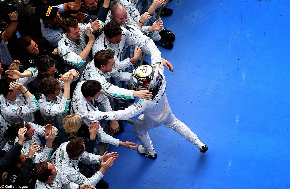 Winning: Hamilton celebrates with his Mercedes teammates having claimed a commanding victory