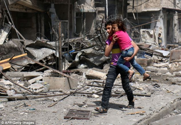 A Syrian youth carries a girl to safety following a barrel-bomb attack by pro-government forces