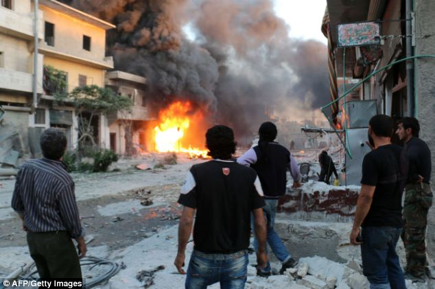Rebel fighters and civilians stand looking at a burning building following a reported barrel bomb attack by Syrian government forces in the northern city of Aleppo