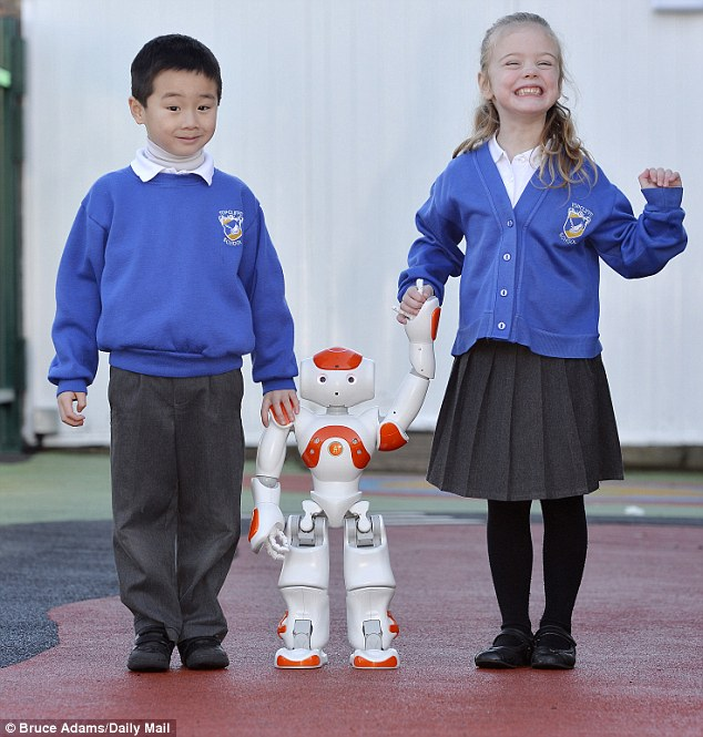 Topcliffe School in Castle Vale, Birmingham, West Midlands has become the first school in the UK to use a robot to teach autistic children. Pictured are pupils Corbin Chow (left), five, and Libi Cooper (right), five, taking the £15,000 robot named 'Max' for a walk