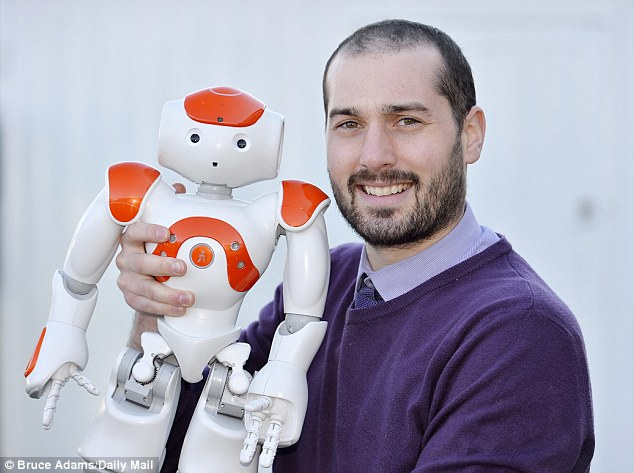 ICT Leader Ben Waterworth, 28, stands with 'Max' the robot at the mainstream state school, which has a centre dedicated to those with autism
