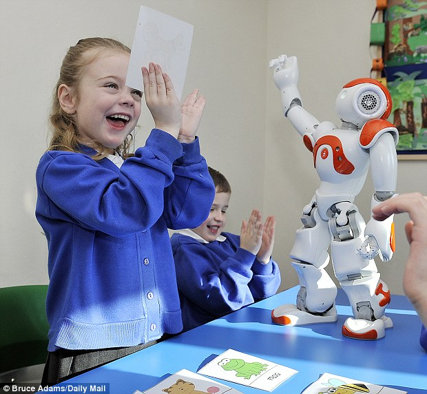 Pupils Libi Cooper, 5, and Kyran McKeown, 6, learn while playing with 'Max' the robot at Topcliffe School