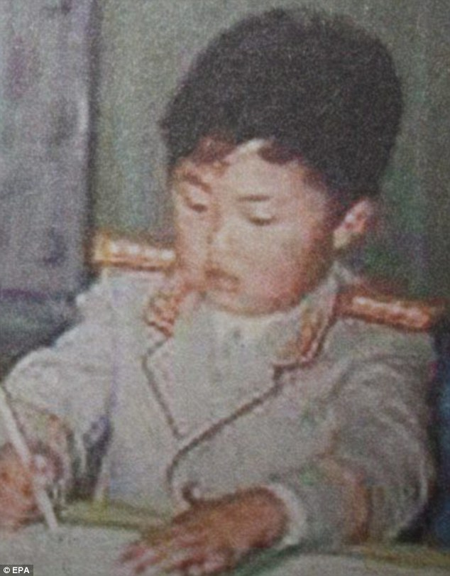 Is he writing his manifesto? Again pictured in a military-style outfit, a young Kim is shown writing or drawing in this picture released by the North Korean Central Television (KCTV)