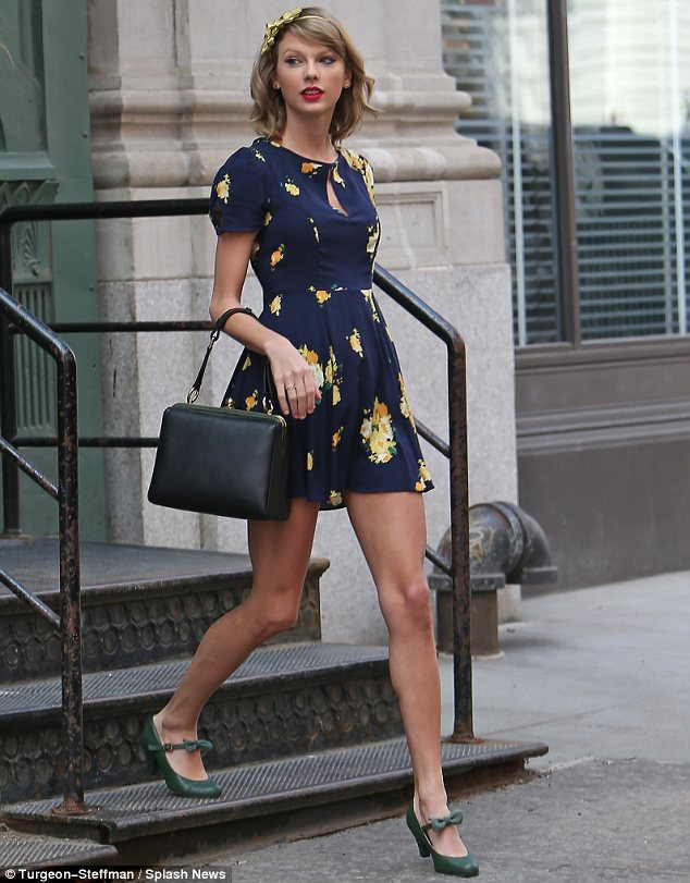 Petal power: Taylor Swift looked adorable in a yellow floral headband and navy sundress on Tuesday