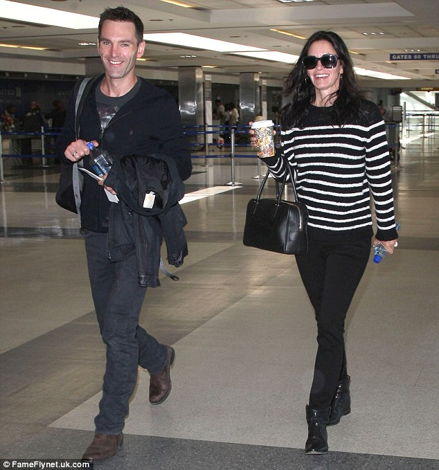 Engaged after five months?: Courteney Cox was seen at a Los Angeles airport on Sunday wearing a large ring with boyfriend Johnny McDaid at her side