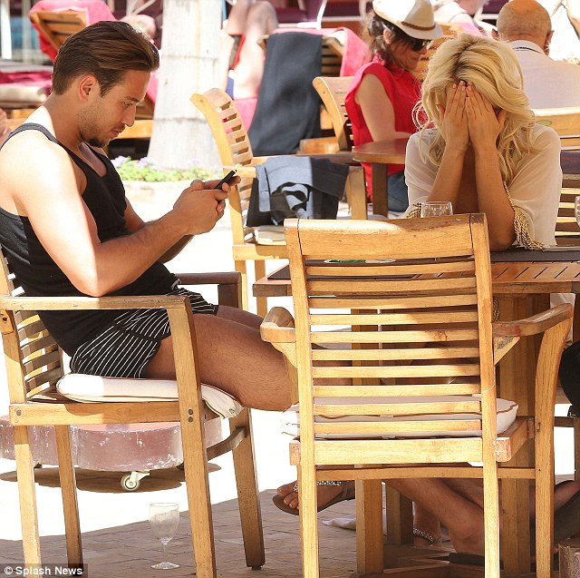Can't face it: Danielle looked exasperated as she buried her face in her hands, whilst James seemed more interested in his mobile while the pair were in Morocco