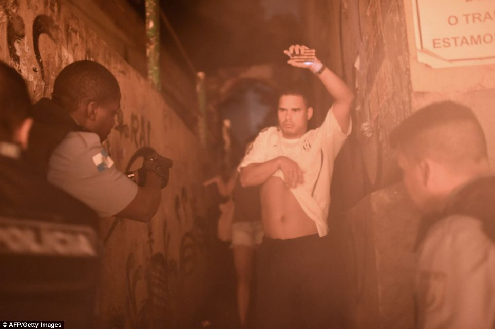 Hands up: Brazilian Police Special Force members detain a man during a violent protest in a favela near Copacabana