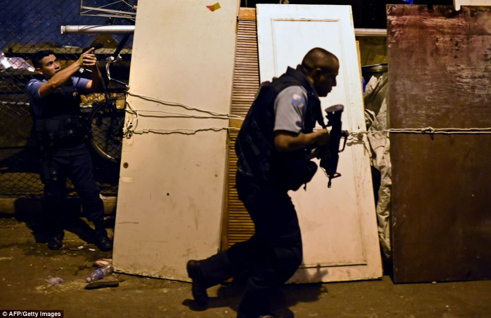 Policemen take positions during the violent protest in the favela next to Copacabana, Rio de Janeiro on Tuesday
