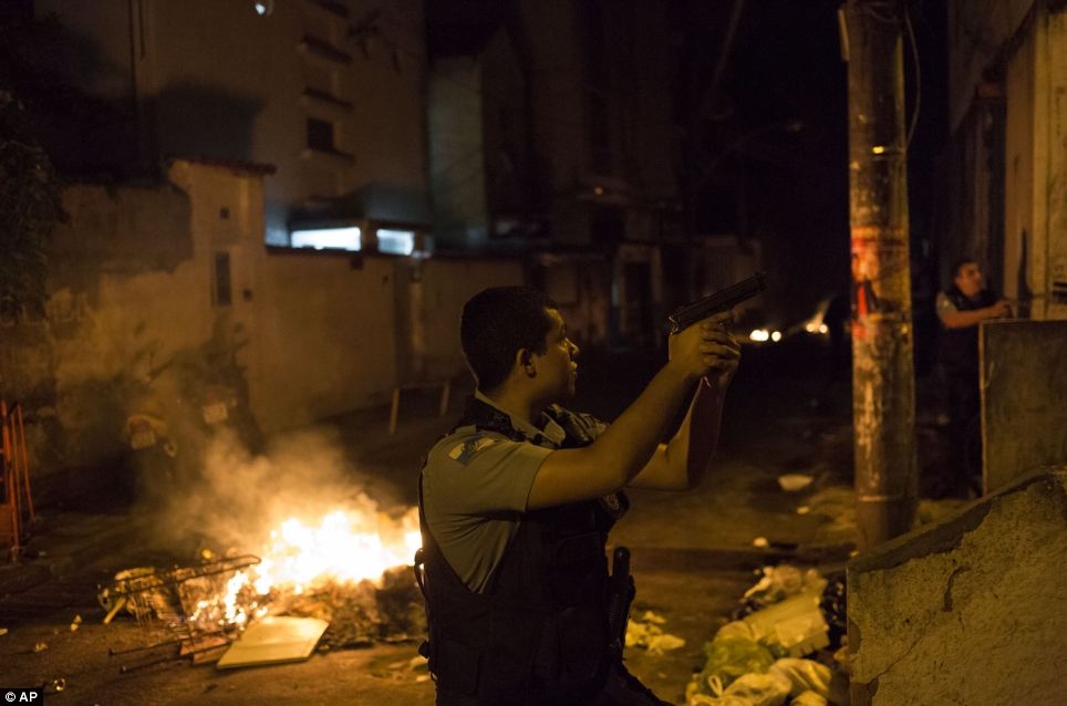 Officers of the Police Pacification Unit patrol next to a burning barricade during clashes at the Pavao Pavaozinho favela