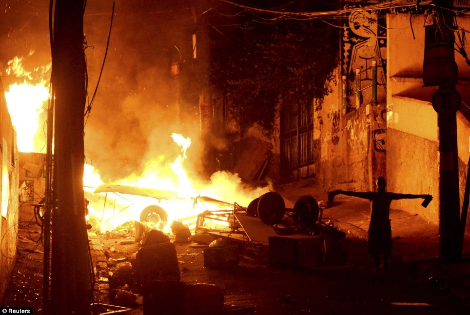 A resident stands beside a burning vehicle during a protest against the death of a man in Pavao-Pavaozinho, in the Copacabana neighborhood in Rio de Janeiro