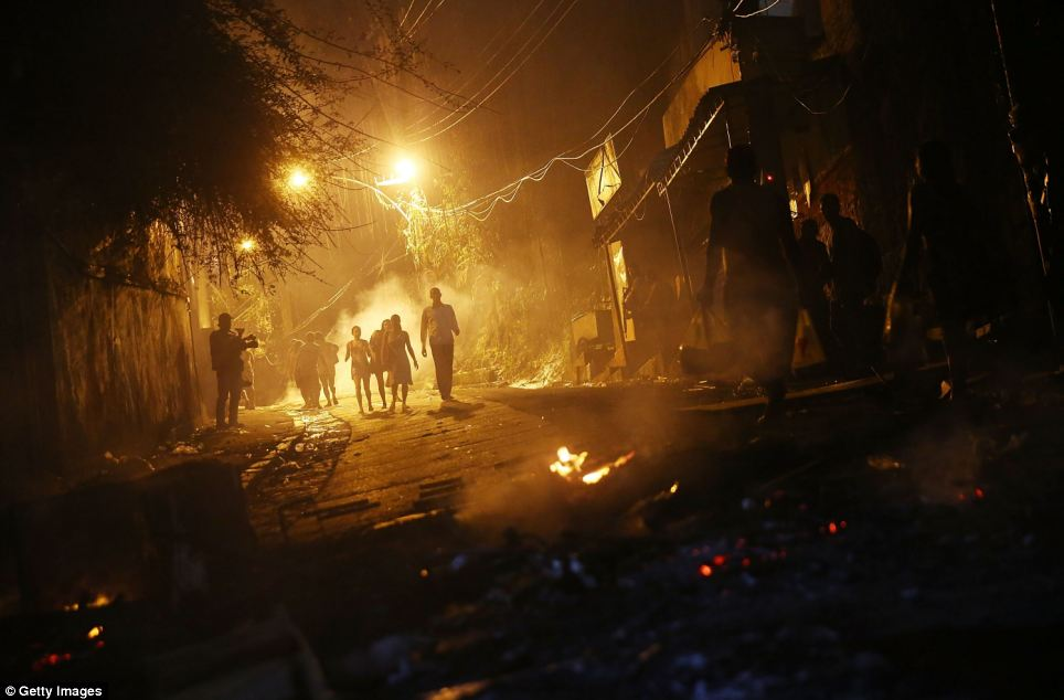 People walk through smoke from fires lit by protesters following shootings in the Pavao-Pavaozinho community, just blocks from Copacabana Beach, on Tuesday