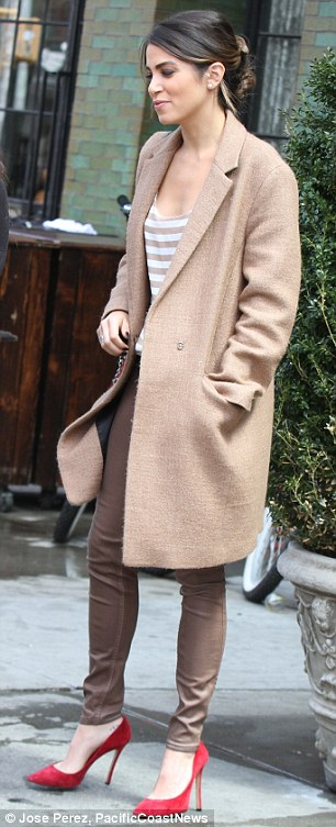 Effortlessly chic: The star opted for brown leather pants, a white and brown striped spaghetti-strap top, a long caramel-coloured winter coat and watermelon suede stilettos, while she carried a black leather handbag on a long strap over one shoulder