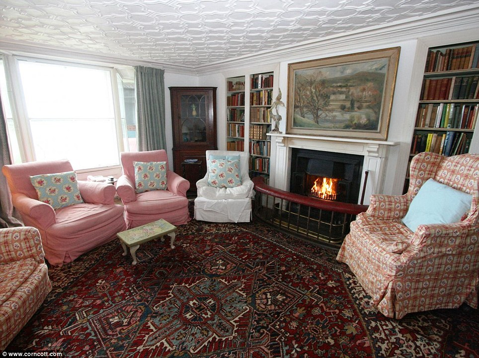 Cosy cottage: One of the lounges in the property features sofas and a roaring fire