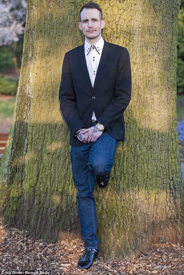 Motionless: Other shots show him posing with his back up against a tree in the cemetery as he stands there with no expression on his face