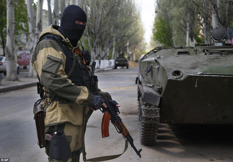 Standing guard: A pro-Russian masked gunman patrols a street  in the center of Slovyansk, eastern Ukraine