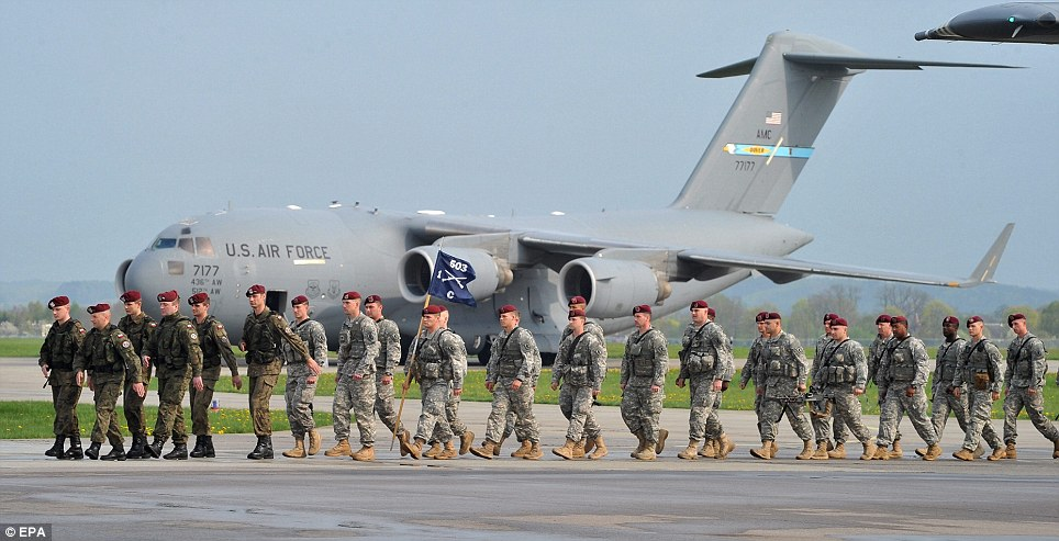 United front: Polish soldiers (left) accompany U.S Airborne soldiers upon their arrival at Swidwin, northern Poland