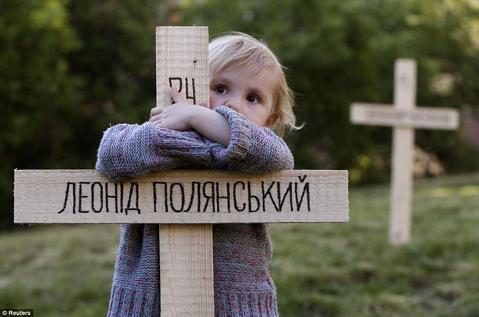 In memory: A child embraces one of the 107 wooden crosses in Prague which honour victims of the recent protests in Ukraine