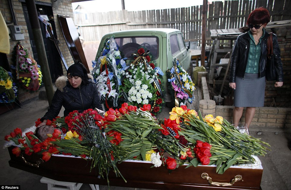 Heartache: The wife (left) of Mr Rybak mourns next to his coffin during the funeral